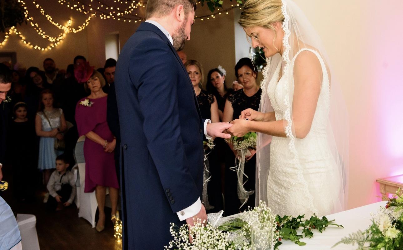 Bride placing ring on husband's finger