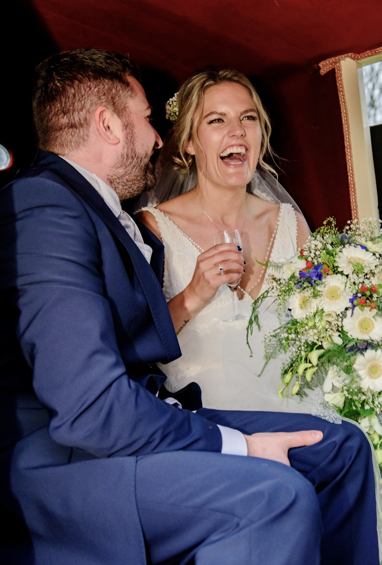 Couple drink champagne in wedding carriage